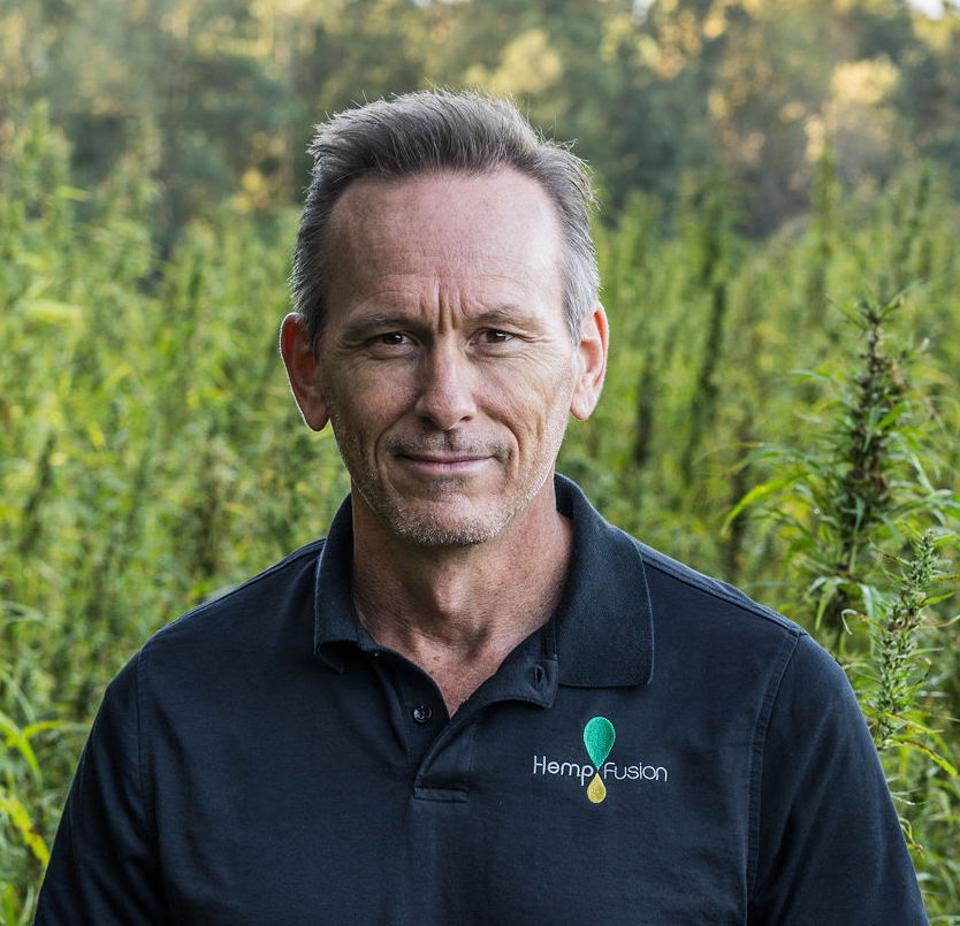 Dr. Jason Mitchell is pictured in a field of hemp.