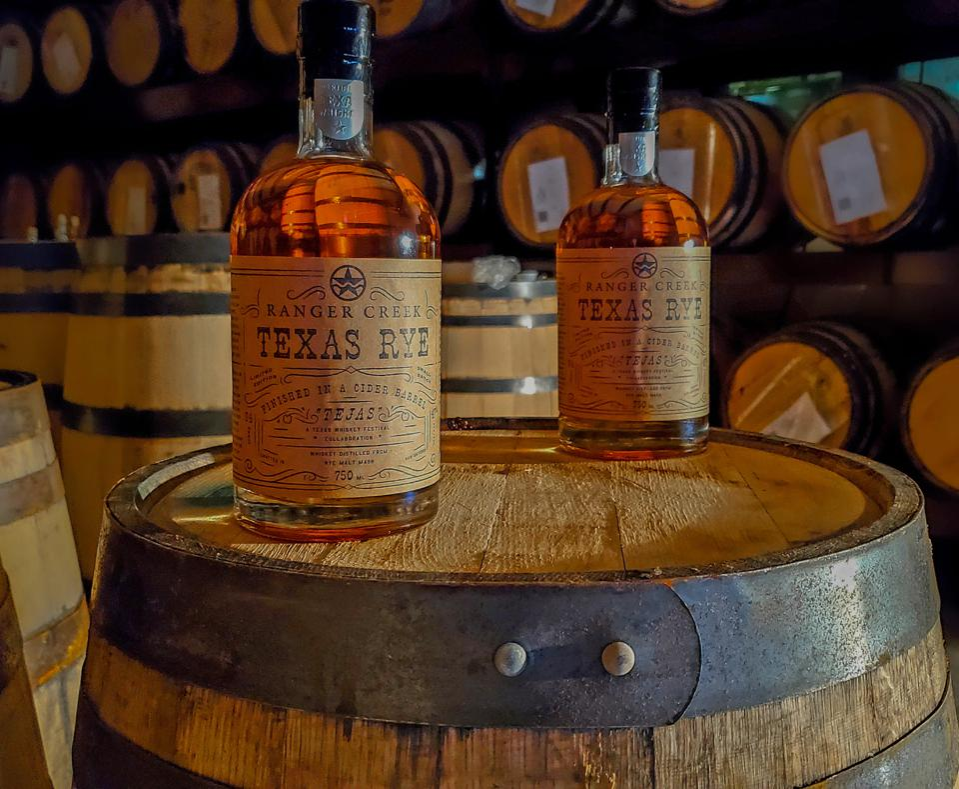 Bottles of Ranger Creek bourbon on top of a barrel