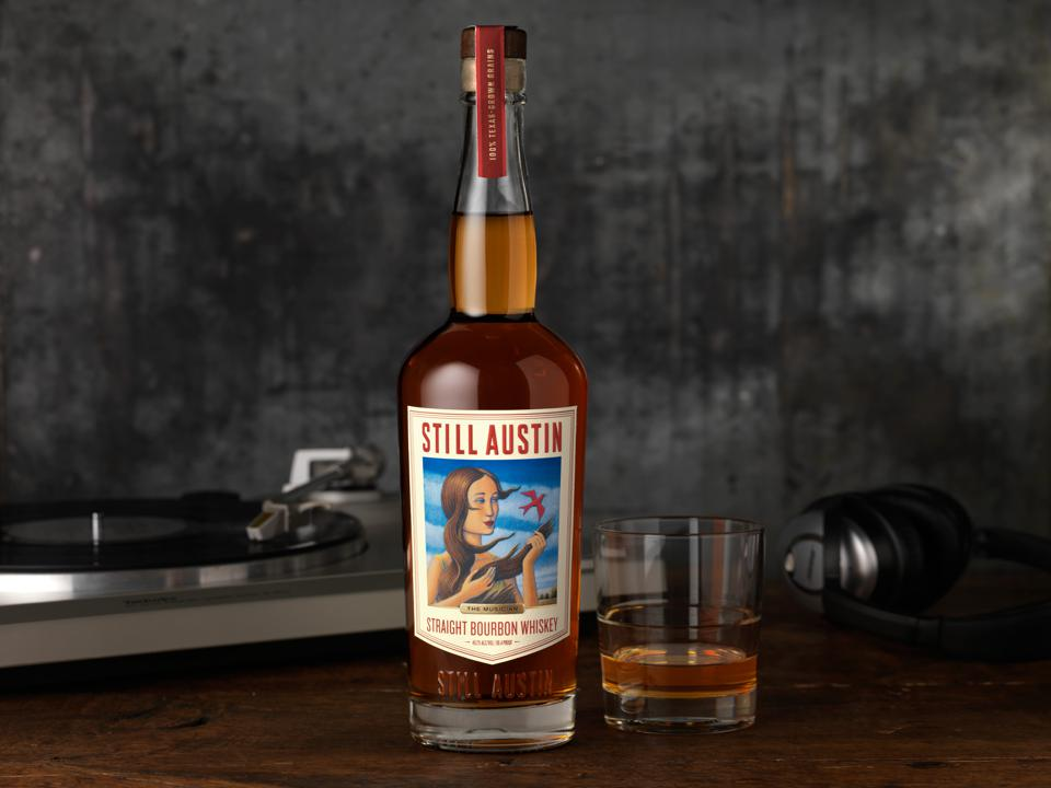 Bottle of Bourbon with glass and turntable in the background