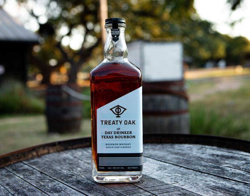 Bottle of bourbon on a barrel outdoors