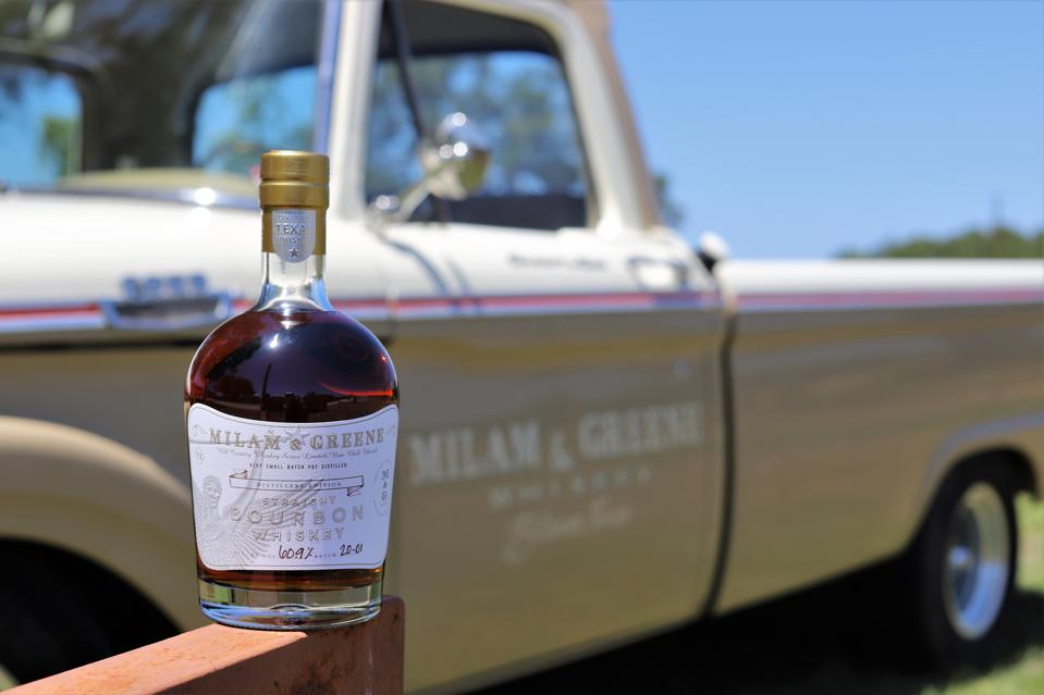 Bottle of bourbon with a vintage truck in the background
