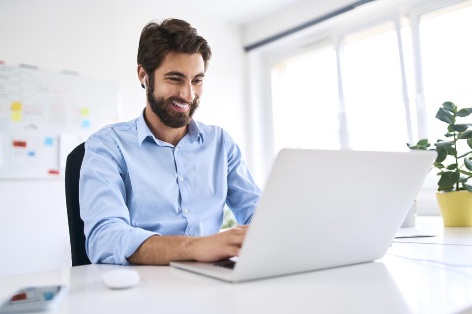 Smiling businessman with headphones sitting at a desk using a laptop