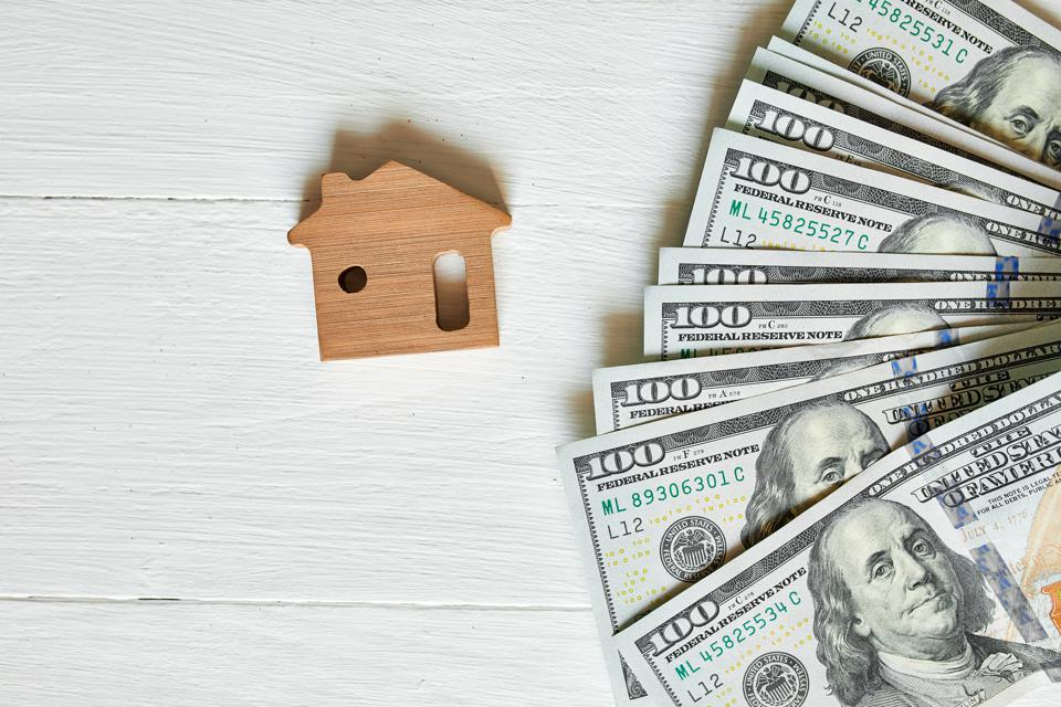 Small wooden house and hundred dollar on white background