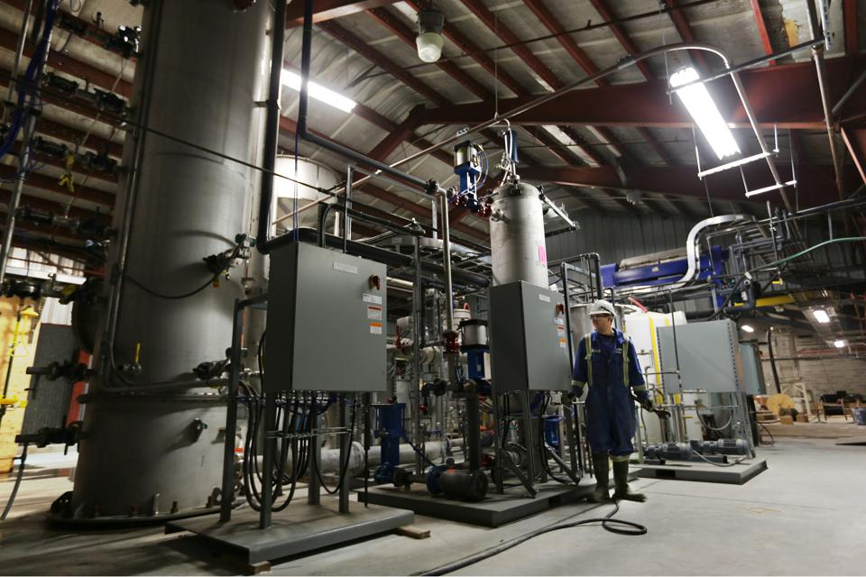 A worker standing near Carbon Engineering's ″pellet reactor″.