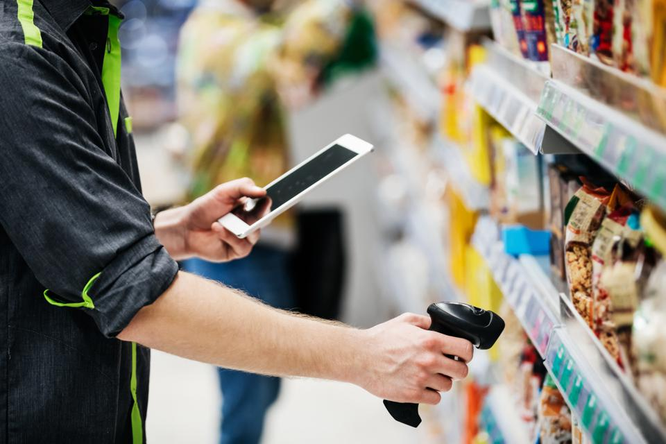 Supermarket Employee Using Tablet And Bar Code Reader