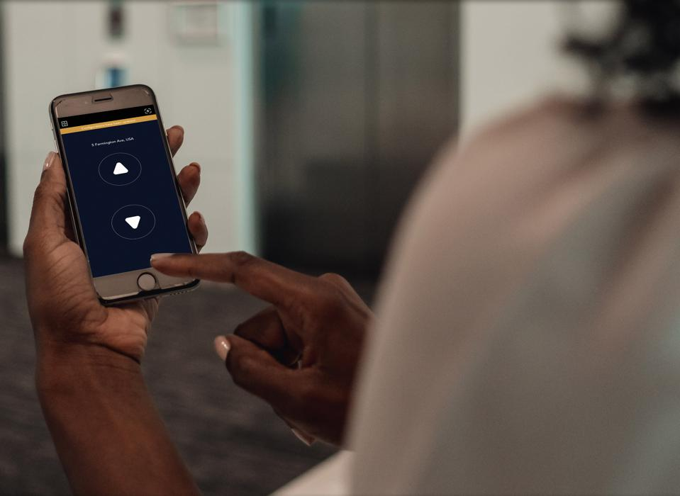 A smartphone users with the Otis eCall app displayed