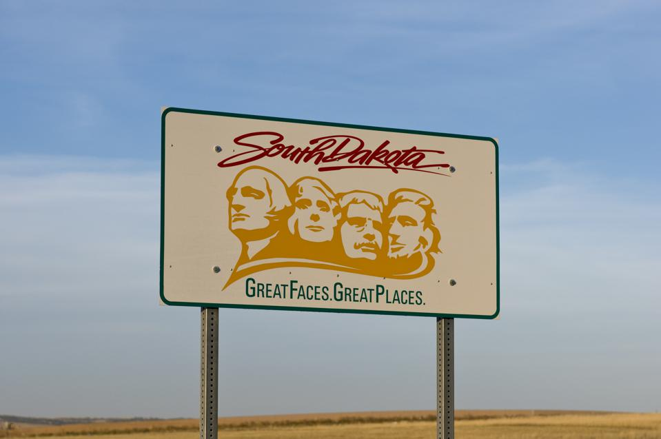 Welcome to South Dakota sign with yellow presidential faces