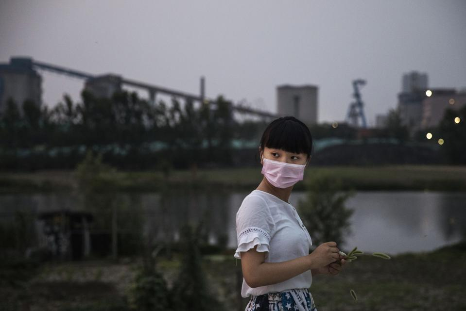 A Chinese girl in a mask walks past a background dominated by a coal fired power plant.