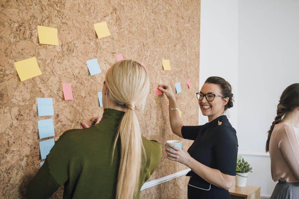 Two Women Making Business Notes On A Cork Board