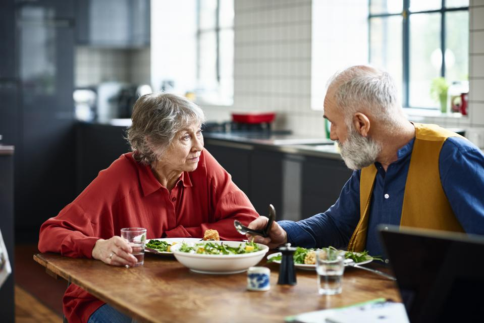 Senior couple having serious discussion over lunch at home