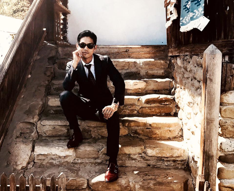 Portrait of Dr. Joseph Yi sitting on steps.