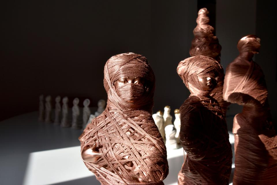 Copper figures of the human form, wrapped in copper thread.