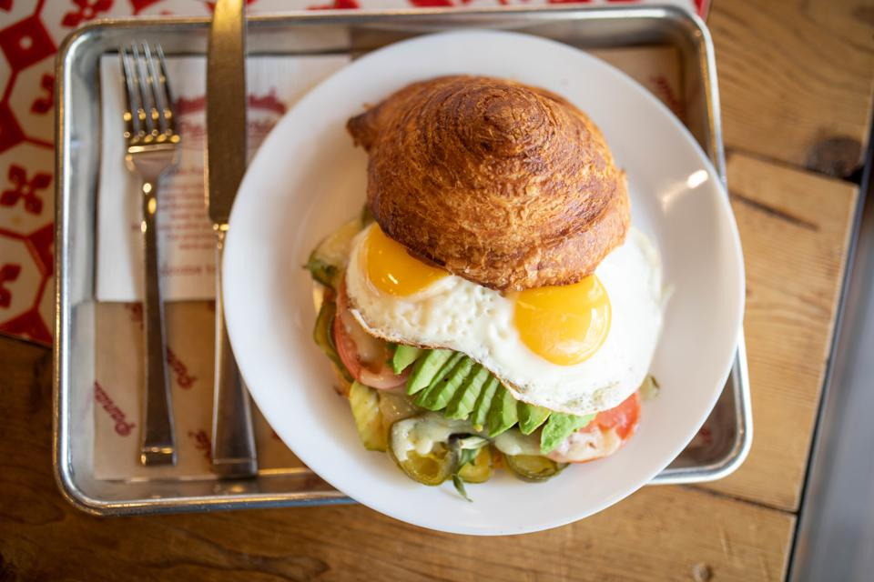 Breakfast plate with eggs and vegetables inside a croissant pastry.