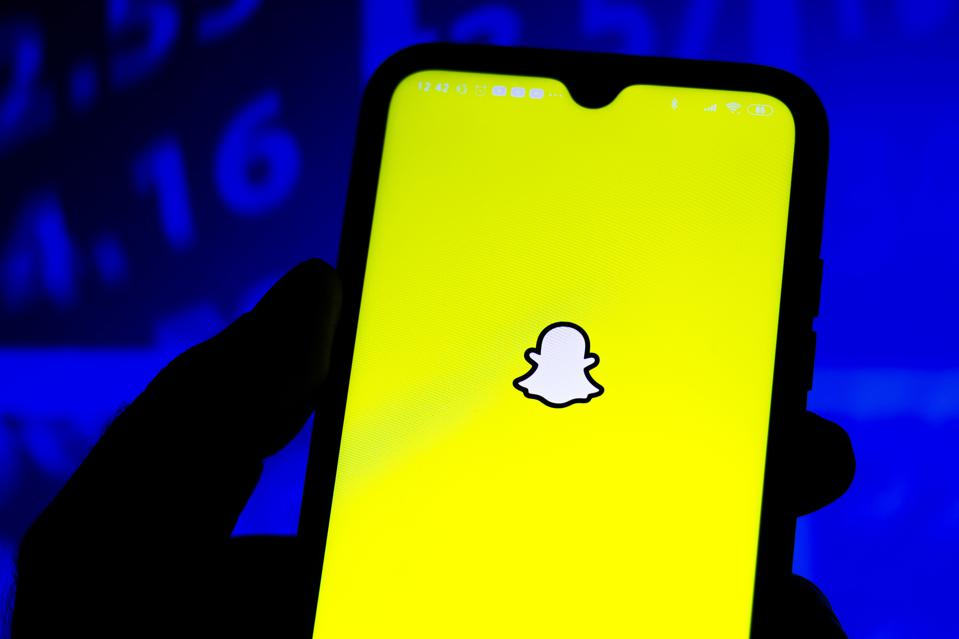 In this photo illustration the Snapchat logo seen displayed...