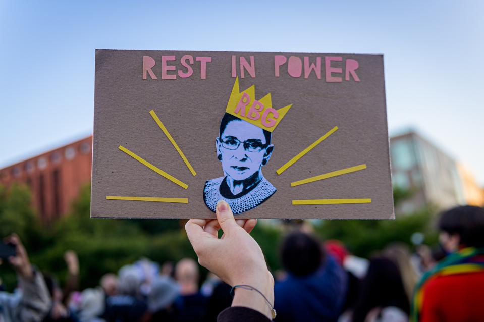 A participant holding a sign at the RBG memorial. A crowd on...