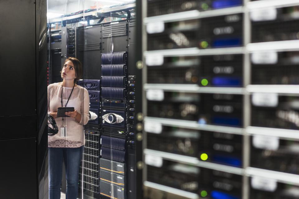 Caucasian technician using digital tablet in computer server room