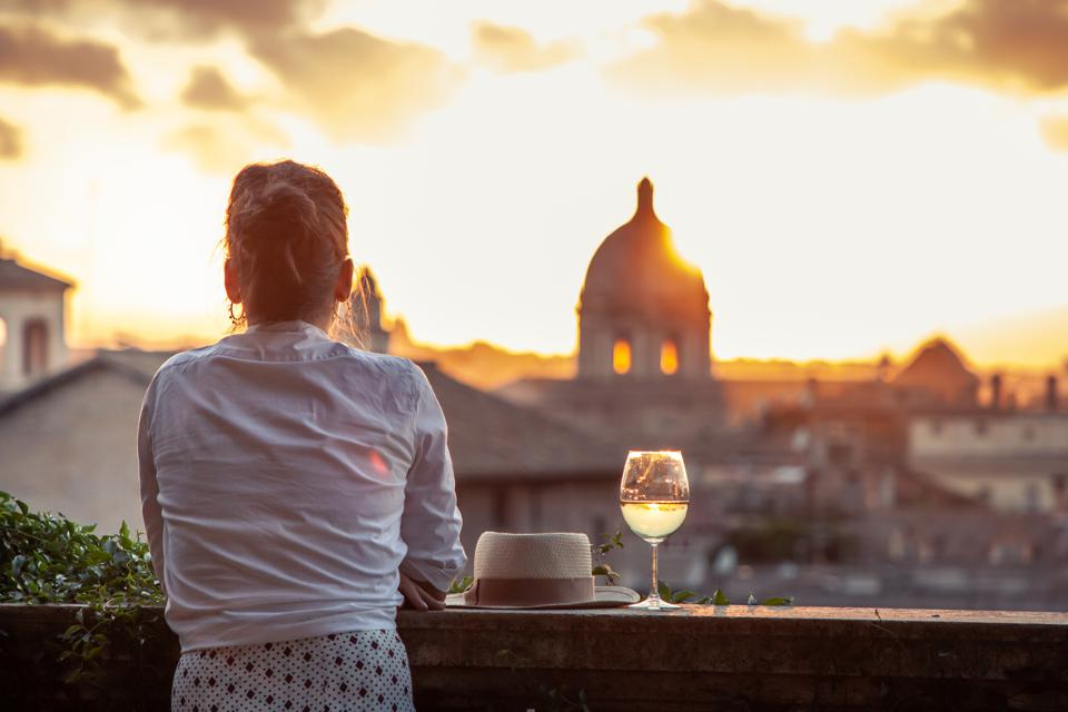 Young woman tourist fashion white dress with glass of white wine in front of panoramic view of Rome cityscape from campidoglio terrace at sunset. Landmarks and domes.