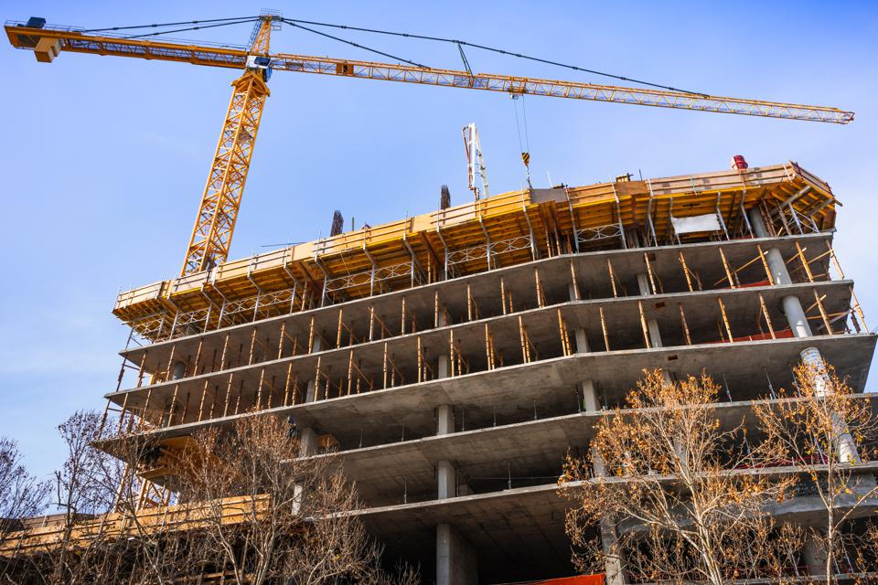 Multi-level concrete building under construction with tower crane; new residential development in the heart of Silicon Valley, San Jose, California