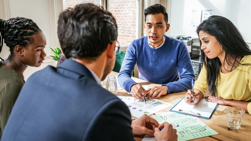 Millennial investors working together at office table