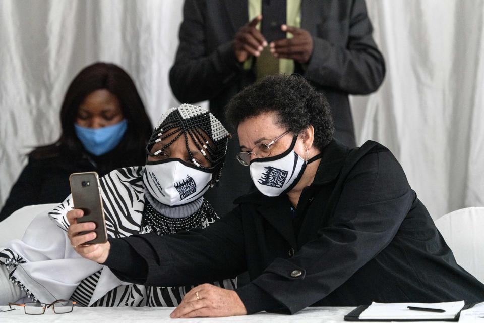 Two women wearing masks take a selfie in a meeting room