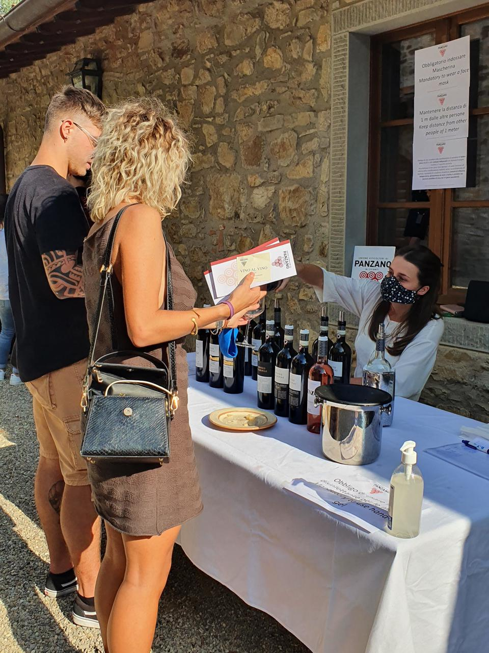 People line up at the tasting table at Vino Al Vino festival in Panzano in Chianti Italy