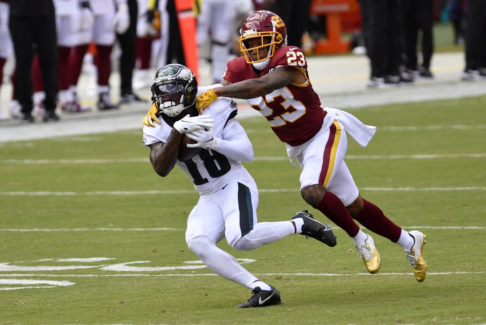 LANDOVER, MD - SEPTEMBER 13: Eagles wide receiver Jalen Reagor (18) makes a deep catch down the middle of the field while Washington cornerback Ronald Darby (23) tackles him during the Philadelphia Eagles vs. Washington Football Team NFL game at FedEx Field on September 13, 2020 in Landover, MD.