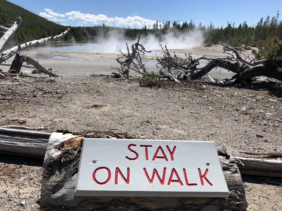 Barren landscape, geyser pools and ″stay on walk″ sign in Yellowstone National Park.