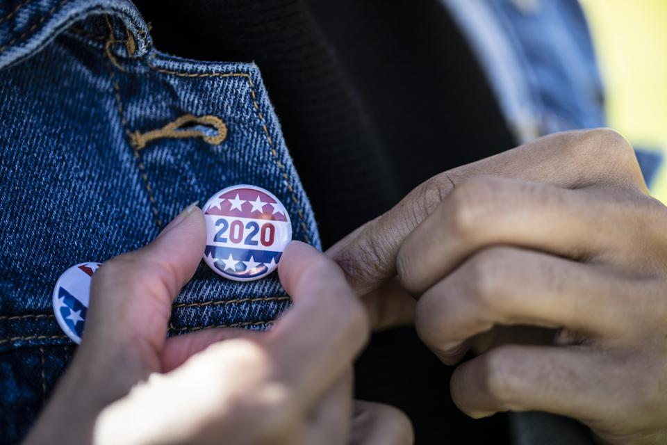 A Black woman holds a 2020 election pin. Hotels are helping guests register to vote.
