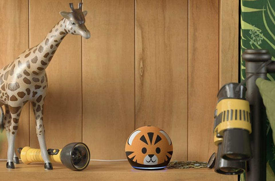 Tiger themed Echo Dot device on kid's bedroom shelf with plastic giraffe toy and wooded decor.
