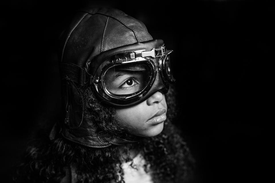 A little girl wears an aviation cap and glasses