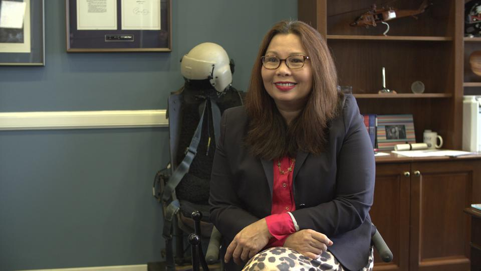 Senator Tammy Duckworth sits in a chair in her office