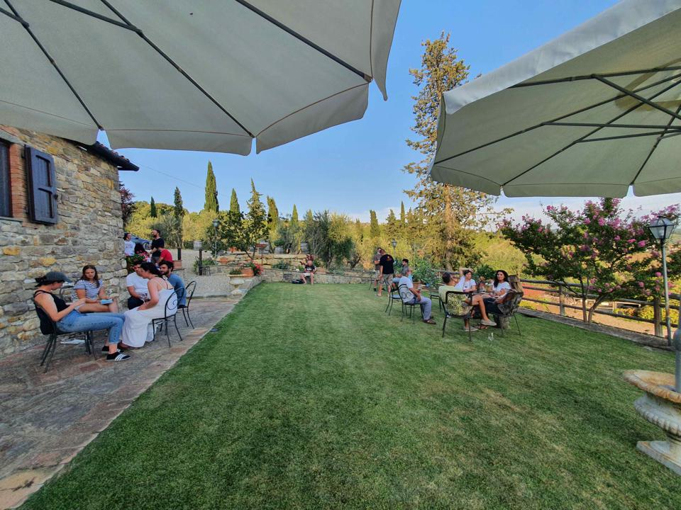 wine tasters sit at tables on the lawns of Chianti Classico winery Il Palagio in Panzano