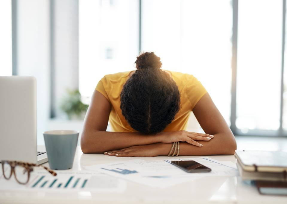 Woman with head down on desk, exhausted by her networking efforts.