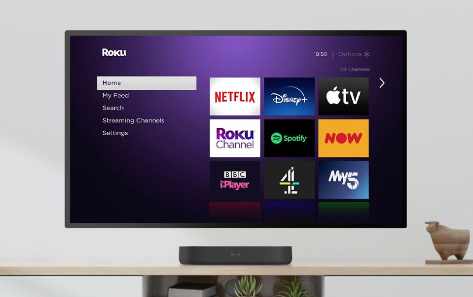The Roku Streambar sat beneath a wall-mounted TV showing icons for Netflix, Disney+, Apple TV, Spotify and more.