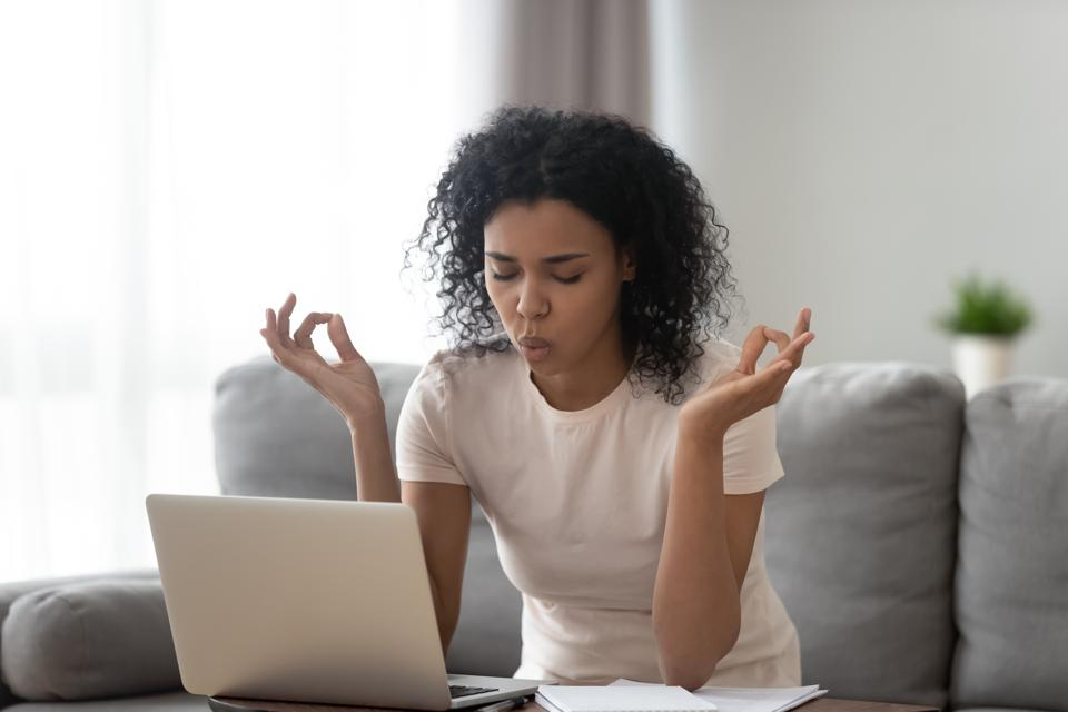 Woman sitting on couch taking breath and meditating in front of laptop to deal with stress