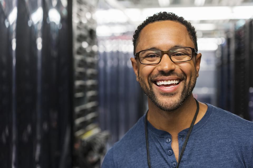 Mixed Race technician smiling in computer server room