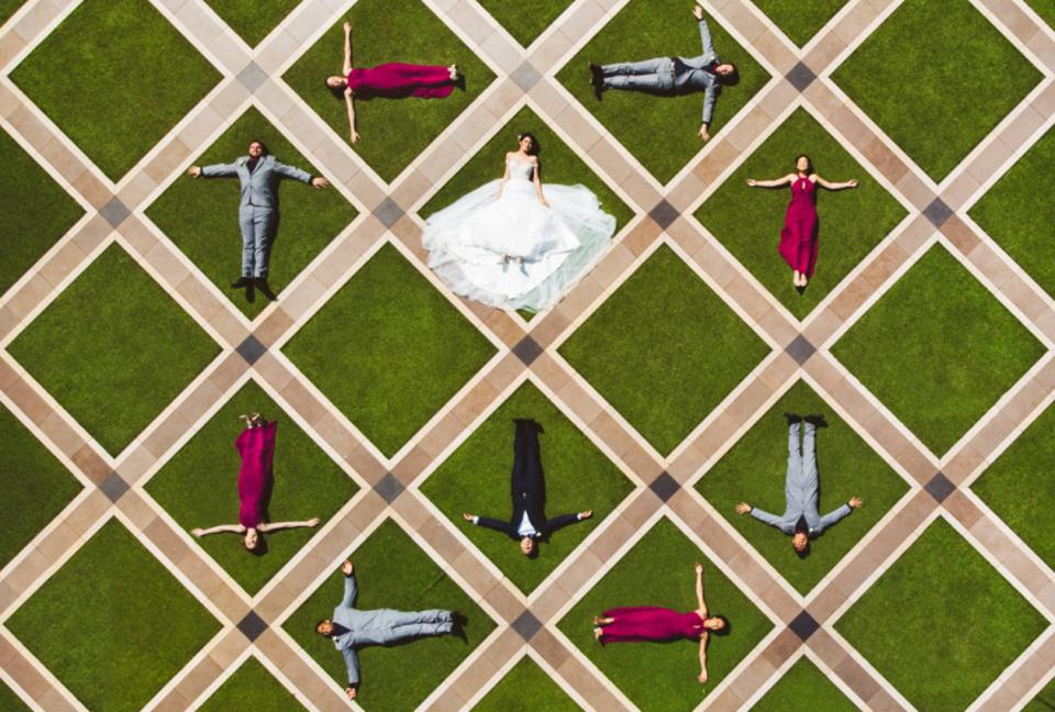 Wedding Photo from above of bride, bridesmaids, and groomsmen .lying down in geometric position