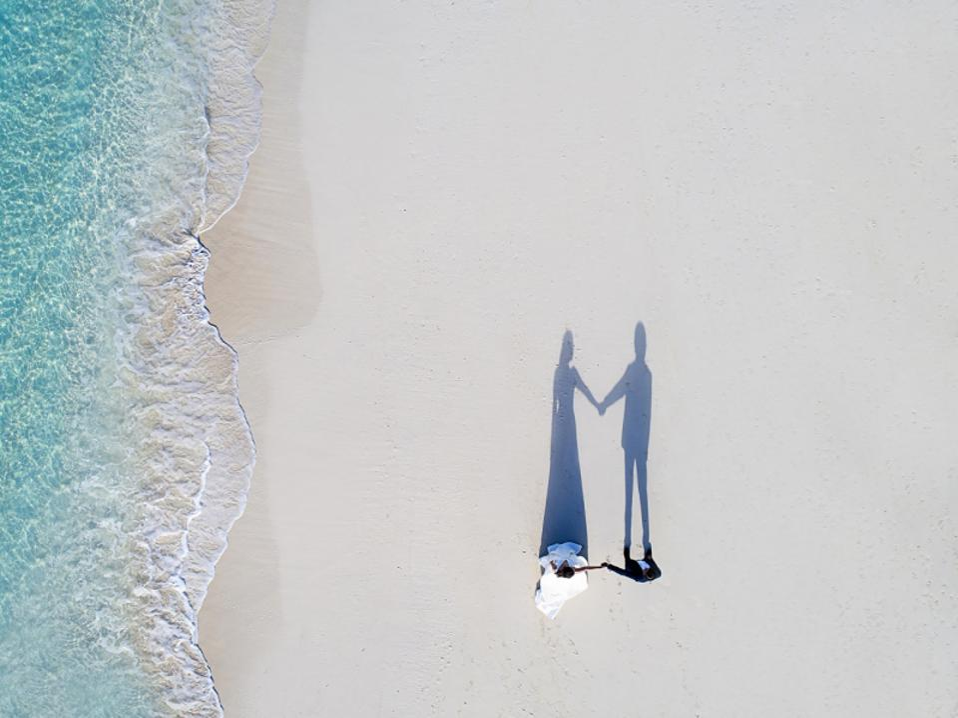 Wedding couple walking on a beach, drone photo.
