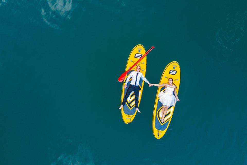 Prize winning wedding photo of couple floating on surf boards taken from above with drone