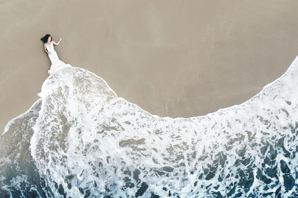 Siena Prize Winning photo of bride by a beach taken from above with drone