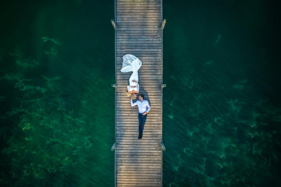 Siena Prize winning wedding photo of couple laying on long dock taken with drone