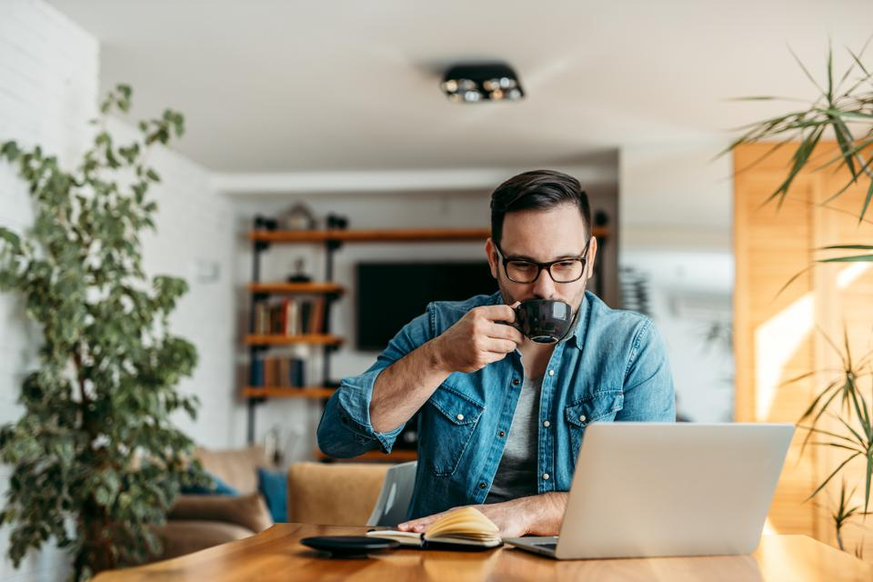 Handsome man drinking cup of coffee and looking at laptop at home office, portrait.