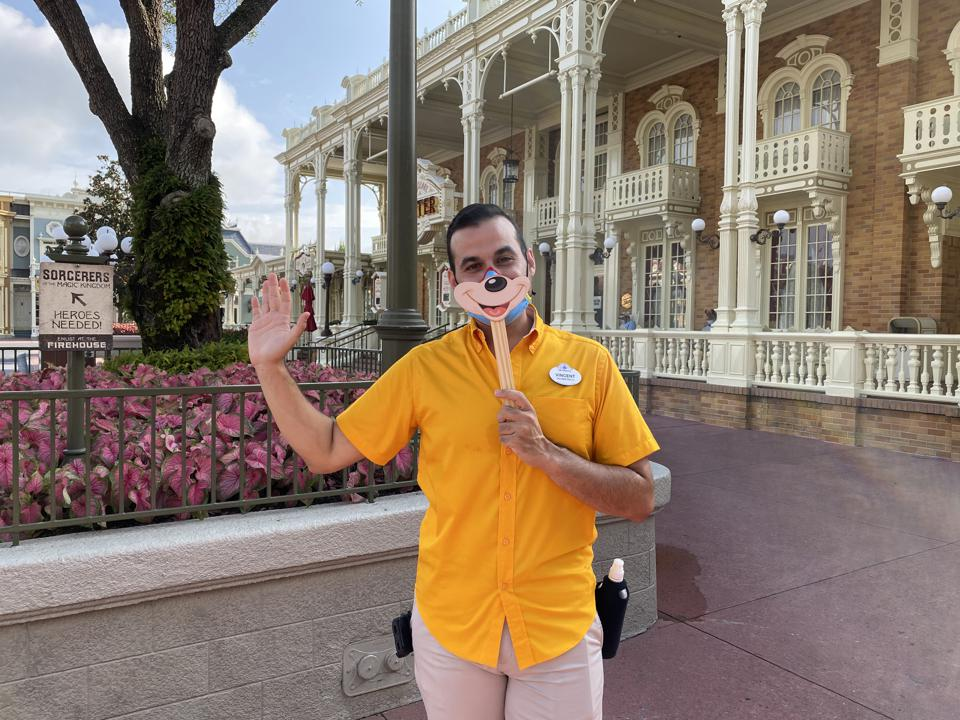 Cast members in Magic Kingdom sometimes hold up character masks in front of their protective masks