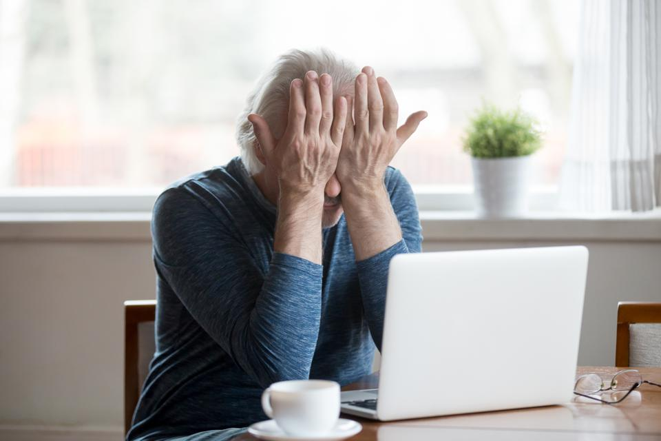 Fatigued senior man feeling tired from computer rubbing irritated eyes