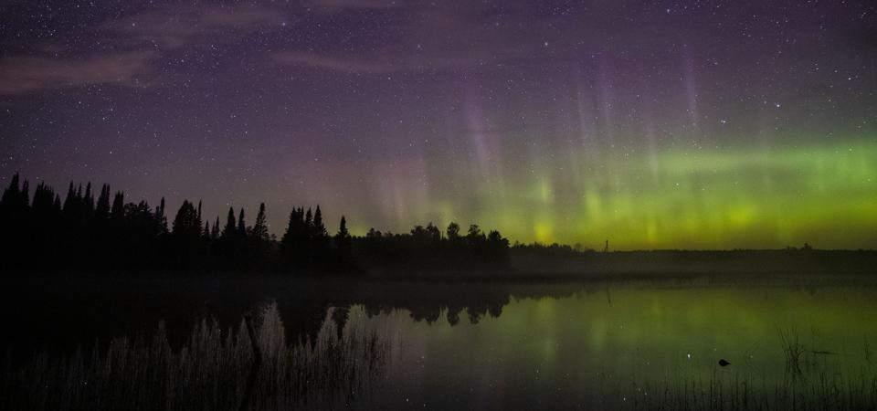 The aurora borealis on the north horizon over Wolf Lake in the Cloquet State Forest in Minnesota around midnight last September 2019.