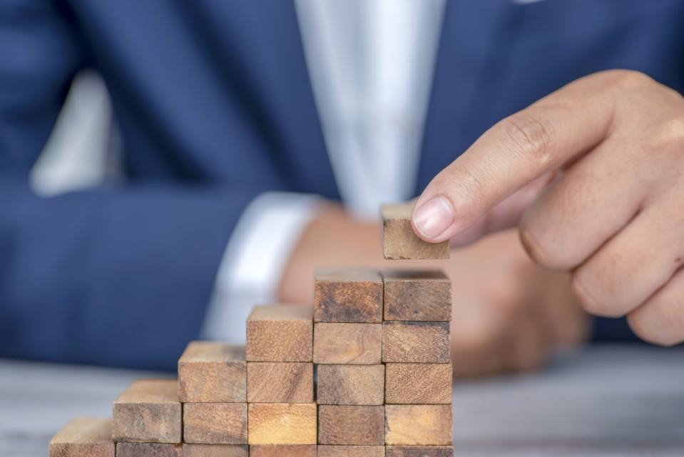 Closer up hands of businessmen,stacking wooden blocks into steps,Concept of business growth success