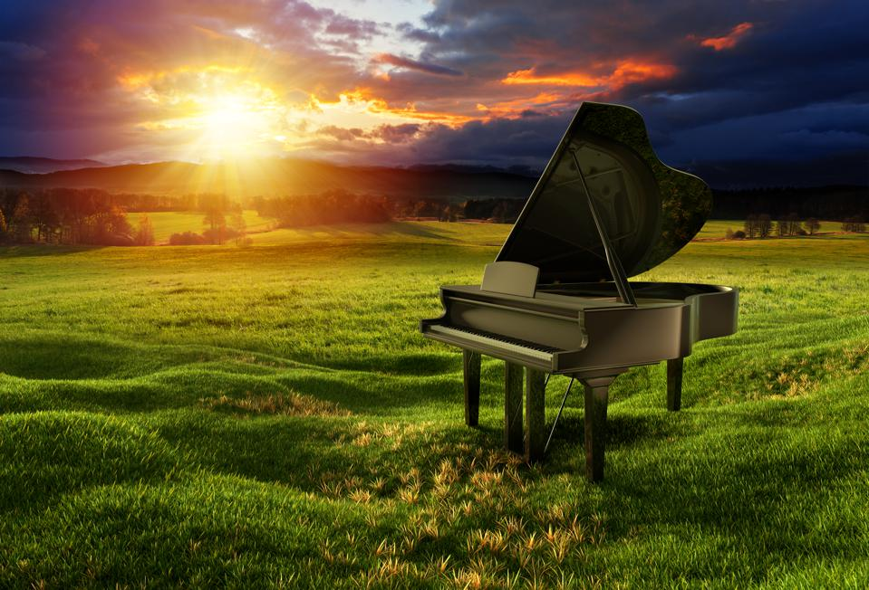 Black glossy piano on the meadow under the dramatic sky
