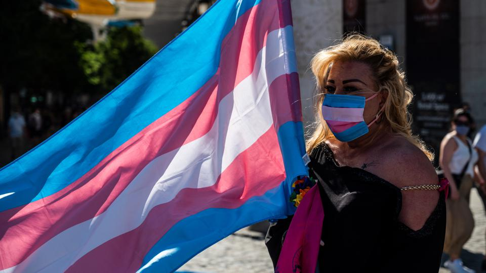 Demonstrator with the Trans flag attends a protest where...