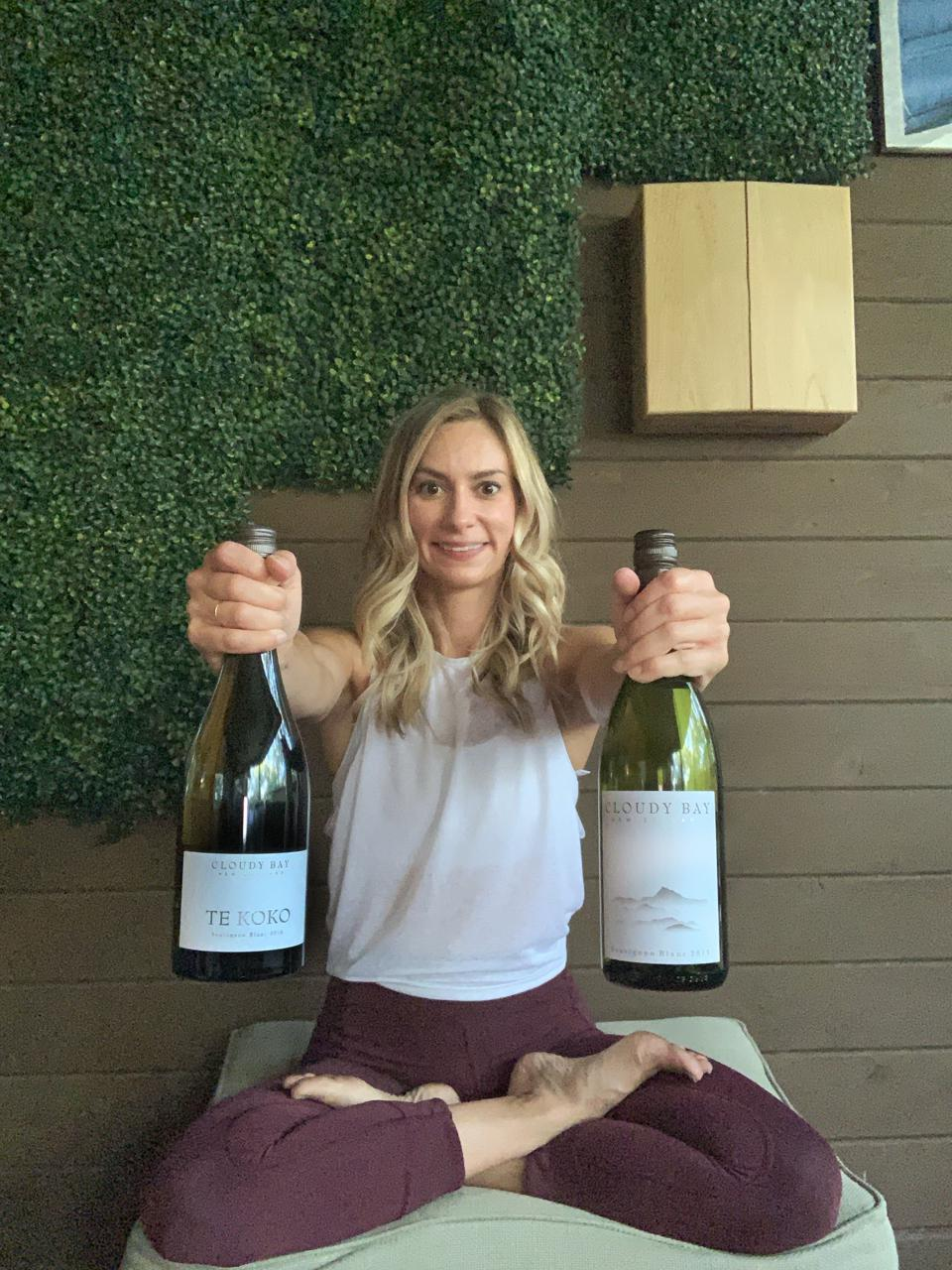 yoga instructor sits cross legged holding two bottles of Cloudy Bay wine for her flow