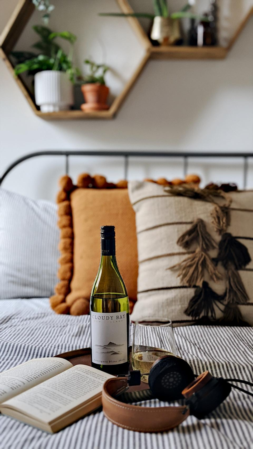 a bottle of wine sits on a bed with head phones and an open book for yoga and meditation